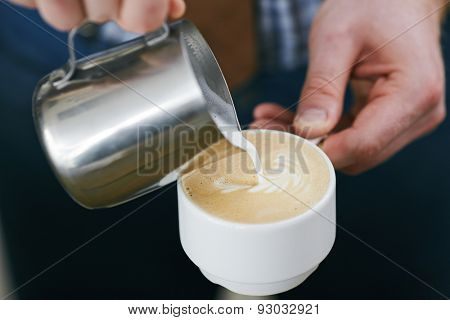 Barista pouring milk from metallic mug in porcelain cup with latte