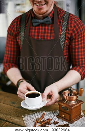 Smiling barista holding cup of black coffee with coffee grinder near by