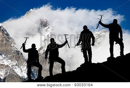 Mount Lhotse And Silhouette Of Men Wirh Ice Axe