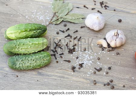 Fresh cucumbers, garlic and spices on wooden table