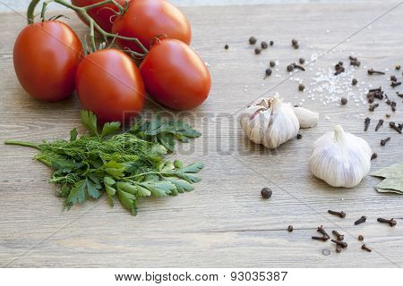 Fresh tomatoes, garlic and spices on wooden table