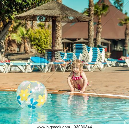 little cute girl sitting near the pool with a ball