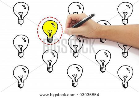 Hand With Pen Drawing Selected Red Dash Circle Around Yellow Light Bulb Idea Among Many On Pure Whit