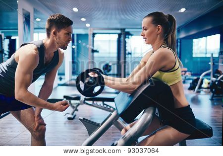 Young woman strengthening arm muscles in gym