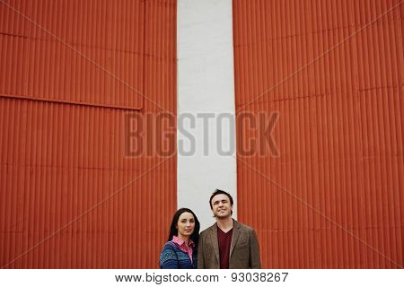Young couple in casualwear standing by wall outside