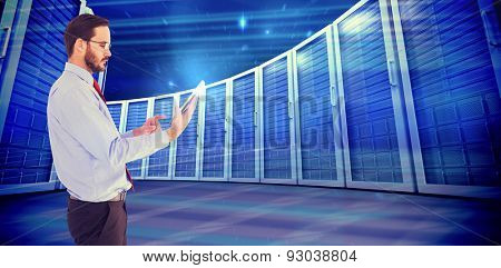 Businessman scrolling on his digital tablet against composite image of server towers