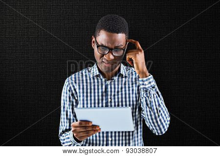 Young businessman thinking and holding tablet against black background