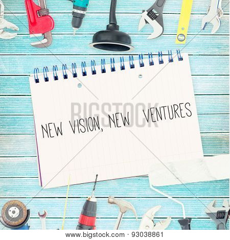 The word new vision, new ventures against tools and notepad on wooden background