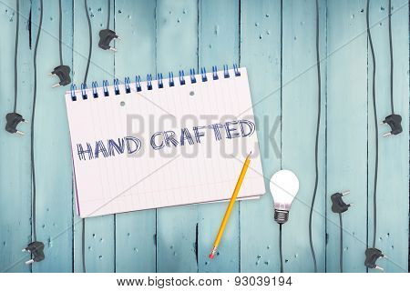 The word hand crafted against notepad and plug on wooden background
