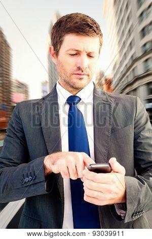 Businessman sending a text message against new york street
