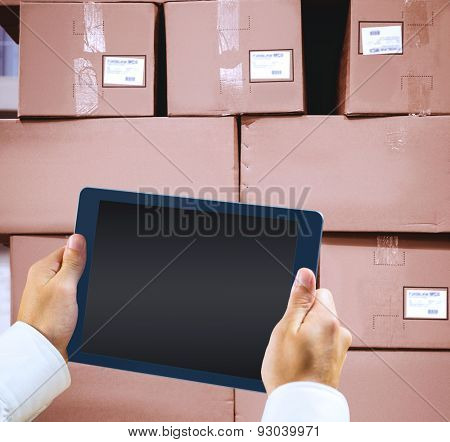 Man using tablet pc against cardboard boxes in warehouse
