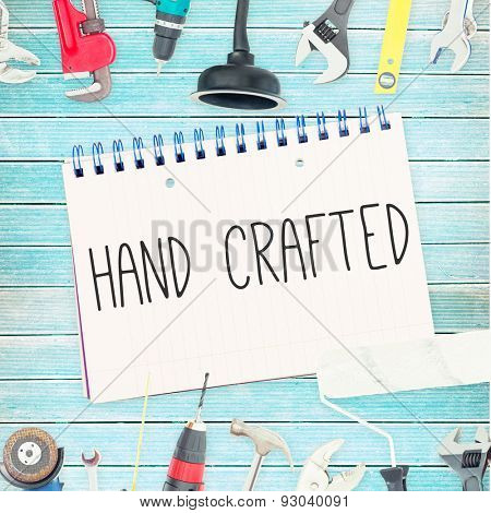 The word hand crafted against tools and notepad on wooden background
