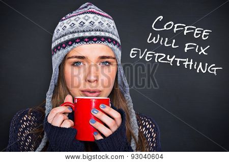 Beautiful woman in warm clothing drinking coffee against black background