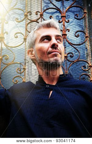 Portrait Of A Sexy Man In Sun Light  And Ornamental Medieval Window On Background.
