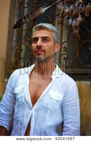 Sexi Man In A White Shirt And Ornamental Window On Background. And Dream Catcher  A Eagle Feather