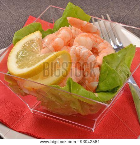 shrimp cocktail on lettuce and lemon.