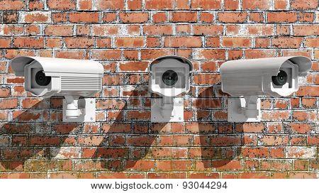 Three security surveillance cameras on brick wall