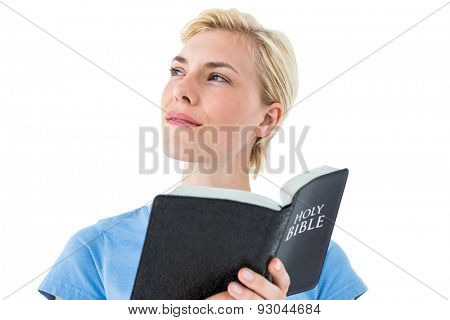 Pretty blonde woman reading bible on white background