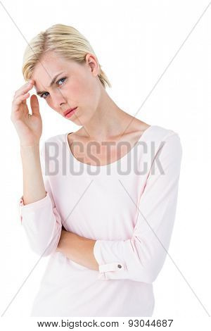 Thoughtful blonde woman looking at camera on white background