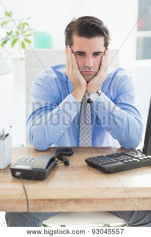 Sad businessman sitting at his desk in the office