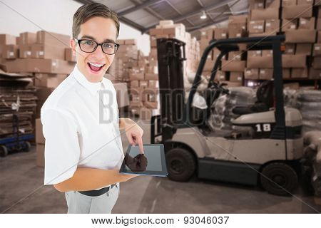 Geeky businessman using his tablet pc against warehouse worker loading up pallet