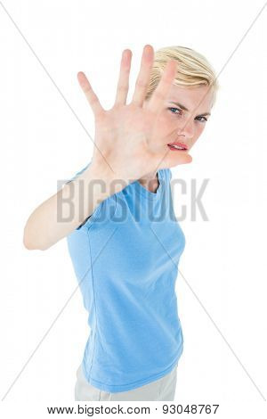 Stern woman gesturing with her hand on white background