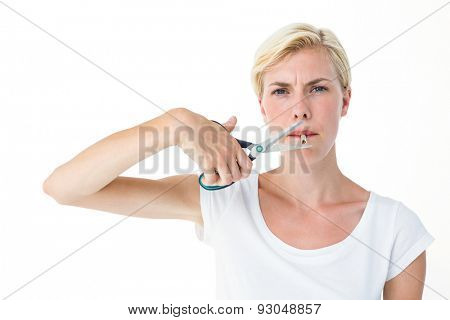 Attractive blonde woman cutting cigarette with scissors on white background