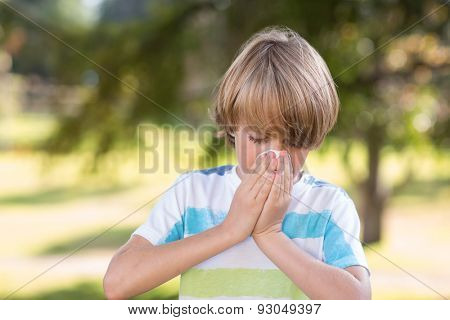 Little boy blowing his nose on a sunny day