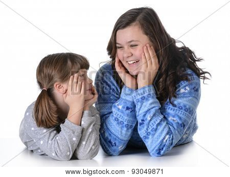 sisters wearing pajamas laying down on white background