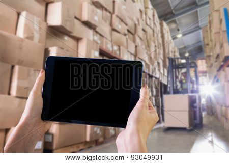 Finger pointing to tablet against forklift machine in warehouse