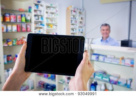 Finger pointing to tablet against pharmacist with grey hair standing behind shelves of drugs