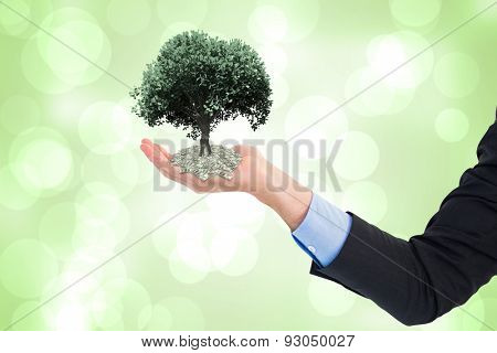 Close up of businessman with empty hand open against green abstract light spot design