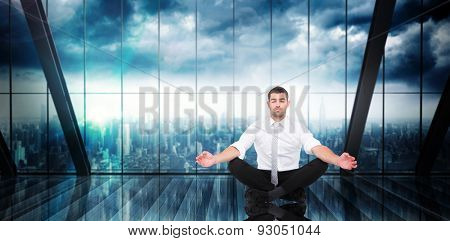 Businessman meditating in lotus pose against room with large window looking on city