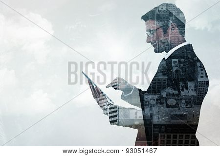 Mid section of a businessman touching tablet against low angle view of skyscrapers