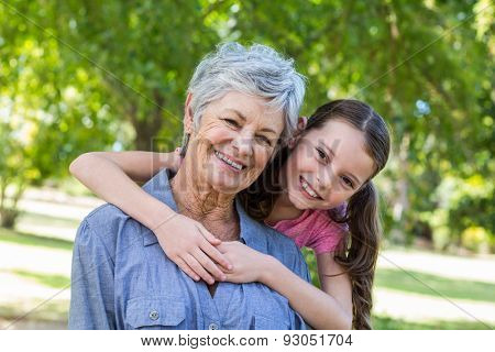 granddaughter and grandmother smiling in a park on a sunny day