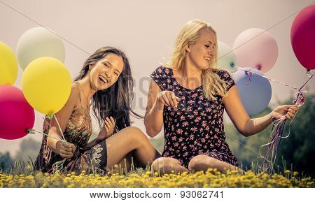 Two Girls Lying In The Grass With Balloons