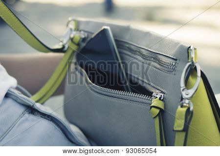 Women's Handbag With The Phone On The Street Close Up