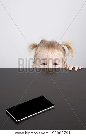 Baby Watching Camera And Phone On Table