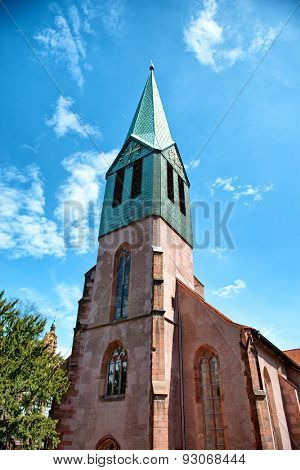 Facade of St Peters old Christian Church built with clock on the green spire in Gothic architectural style, tourist attraction from Heidelberg, Germany