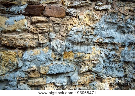 Background texture of an old exterior weathered stone wall with natural rough irregular shaped rocks in mortar