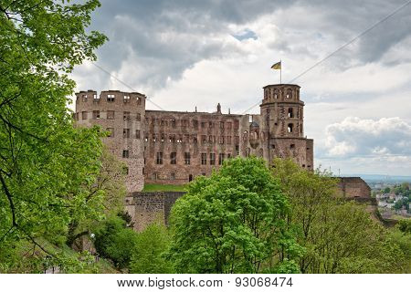 Green vegetation in front of the ruins of Heidelberg Castle, historical tourist attraction, under a dramatic cloudy sky, in Germany
