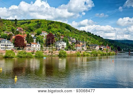 Picturesque houses in Heidelberg, Germany on the banks of the Neckar River reflected in the water under a sunny blue sky with clouds