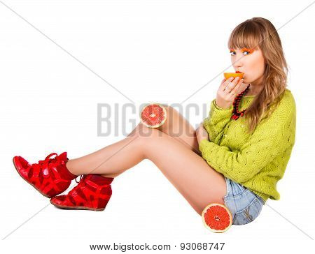 Cute Young Woman In A Green Sweater With Grapefruits Eating An Orange Fruit