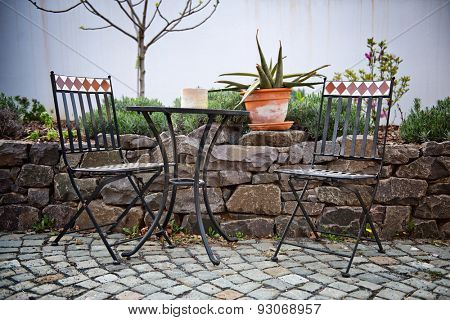 Cast iron garden furniture on a patio with a small table and two chairs standing in the sunshine alongside a walled rock garden with a potted cactus on top of the wall