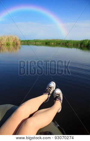Feet In Sneakers On River Landscape With Rainbow