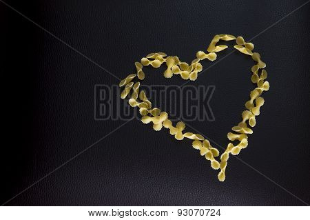 Closeup Of Italian Pasta A Heart Shape, Farfalle Isolated On Dark-brown Background