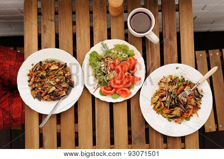 Two Portions Of Porcini Mushrooms Ragout With Vegetable Salad And Red Wine On Wooden Table