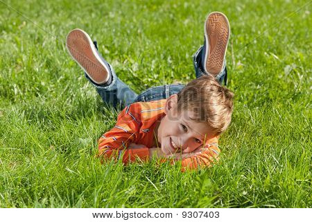 Smiling Boy Lying On The Grass