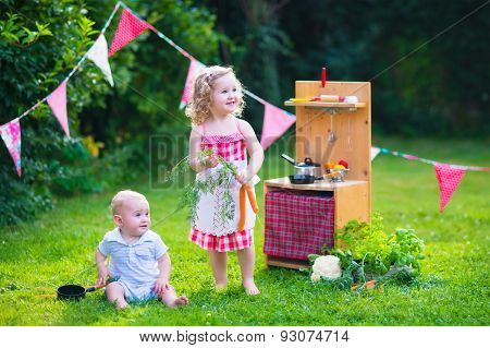 Kids Playing With A Toy Kitchen In A Summer Garden