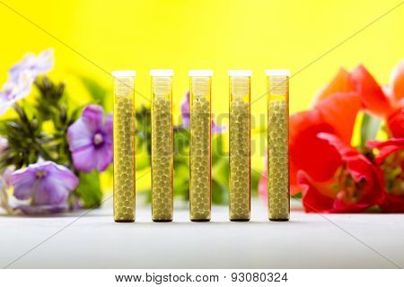 Five Small Glass Tubes With Homeopathy Globules, Yellow Background And Flowers